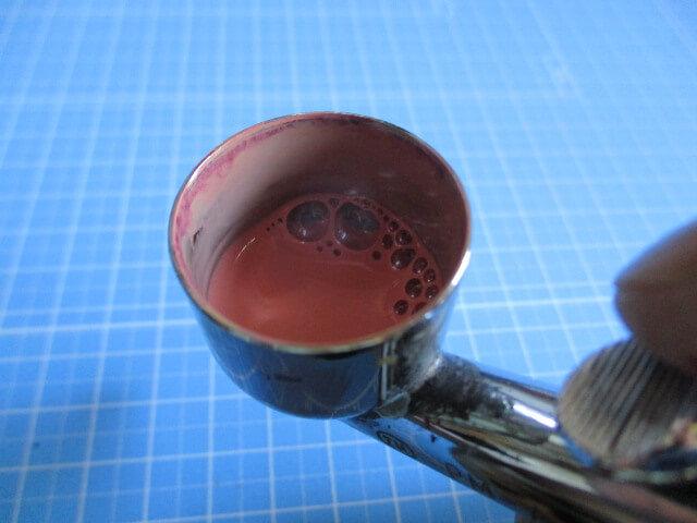 エアブラシのカップに直接うすめ液を入れて稀釈している画像